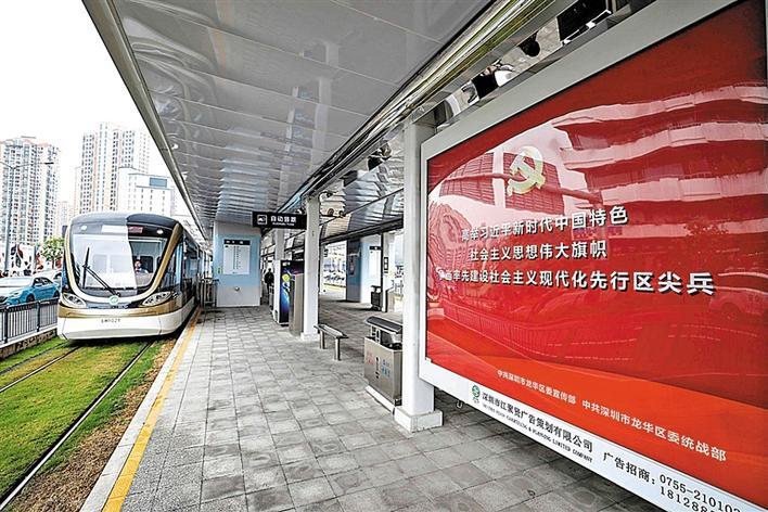 在有轨电车清湖站,宣传党的十九大精神的展板前,吸引不少候车