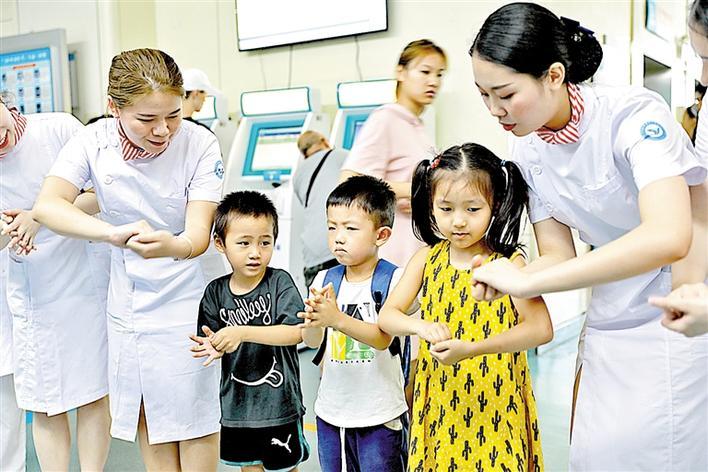 医务人员教小朋友如何正确洗手.