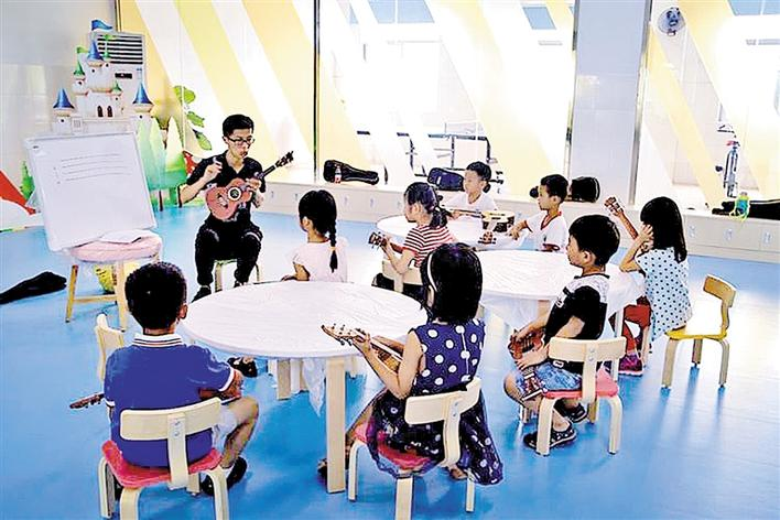 孩子们学习弹奏尤克里里.