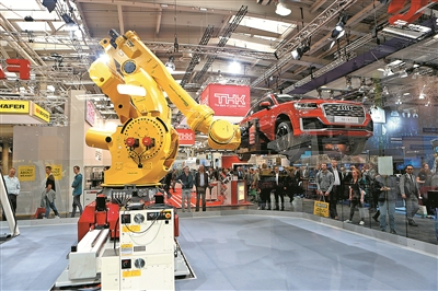 2017德国汉诺威工博会上,智能机械臂将一辆小轿车举在空中并进行现场